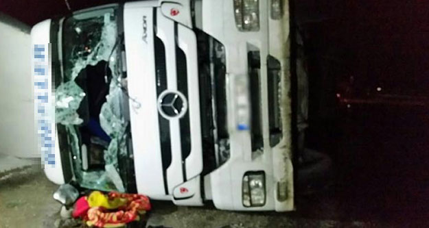 Buzlu yolda kayan kamyon yan yattı